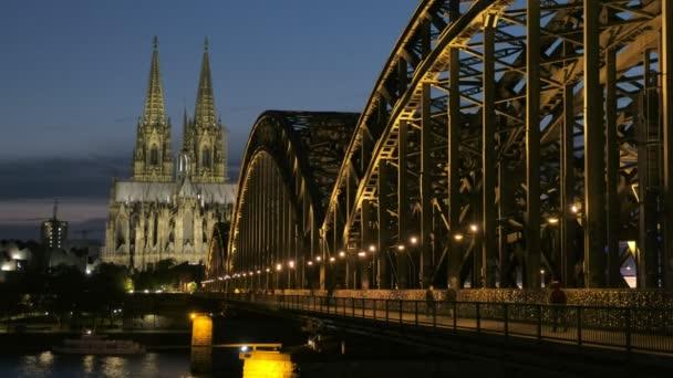 Statische Aufnahme der Hohenzollernbrücke und des Kölner Doms bei Nacht mit eingeschaltetem Licht. Blaue Stunde für Fußgänger