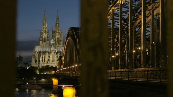 Bei eingeschaltetem Licht steigt die Kamera nachts auf die Hohenzollernbrücke und den Kölner Dom. zur blauen Stunde, wenn der Zug durchfährt