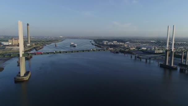 Drone rises slowly beside Queen Elizabeth II Bridge as cargo ship departs Purfleet port