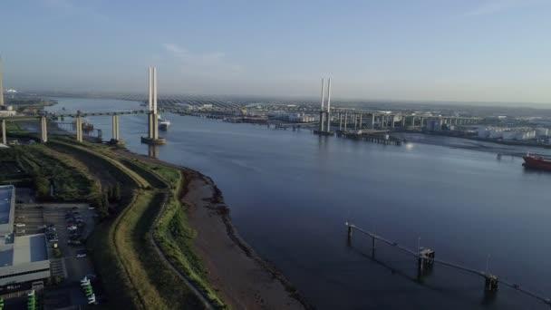Drone flies slowly over bank of River Thames towards Queen Elizabeth II Bridge