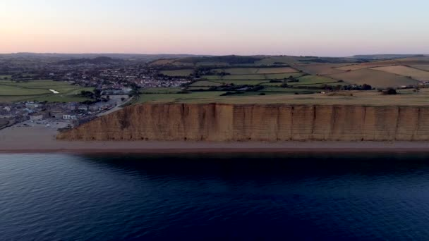 Drone tracks along cliffs and beach to the town of West Bay in Dorset. Shot during golden hour.