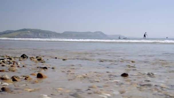 Alacsony szintű dia alatt Sandy Beach Lyme Regis, mint szörfösök fejét, ki. Jurassic Coast sziklák láthatók a háttérben