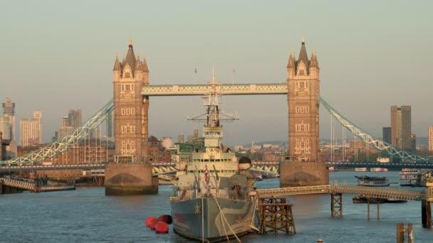 Long static shot of HMS Belfast framed by Tower Bridge. Taken at sundown on a spring evening