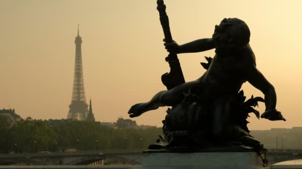 Sculpture on the Alexandre III bridge with Eiffel Tower in the background in Paris, France. Taken during sunset time