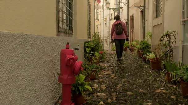 Lisszabon/Portugália-9 május 2019: nő turista sétára a kamera szűk macskaköves Backstreet a Alfama kerületben Lisszabonban