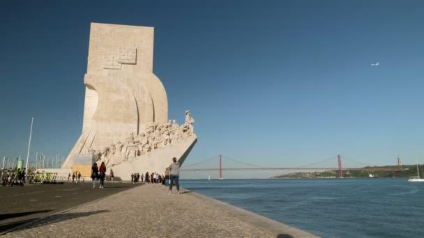 Široká ukázka památníku objevů na břehu řeky Tagus v okrese Belem. 25. dubna Bridge je na pozadí v Lisabonu, Portugalsko