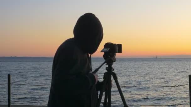 Kapuzenpullover tragende Fotograf macht Fotos vom Sonnenaufgang über dem Schwarzen Meer in Odessa Ukraine
