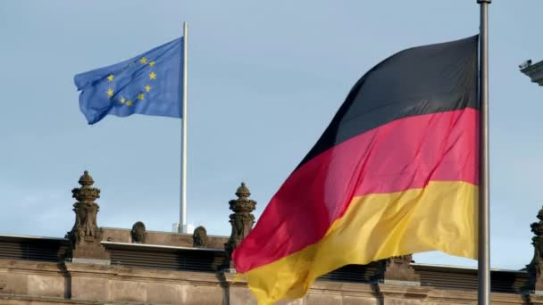 Close shot of German and EU flags flying in strong wind on the German Reichstag