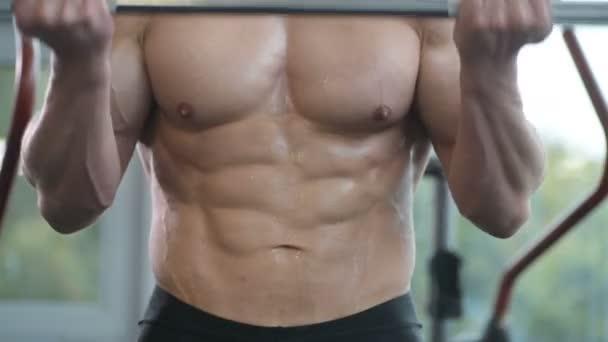 Kaukasischer Kraftsportler, der die Bizeps-Muskeln hochpumpt. Starker Bodybuilder mit Sixpack, perfektem Bauch, Trizeps, Brust, Schultern im Fitnessstudio. Fitness und Bodybuilding-Konzept