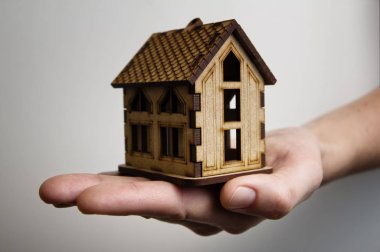 The palm with wooden model house. Concept of rent, purshase, insuranse, building real estate, eco house and other.