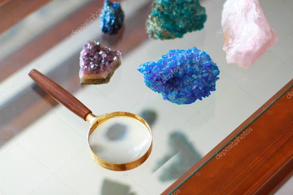 Loupe entouree de pierres prcieuses et pose sur une table en verre