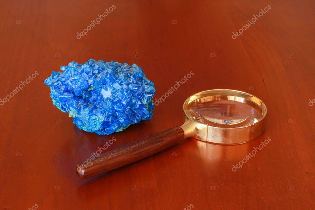 Pierre bleue pose cote d'une loupe dore