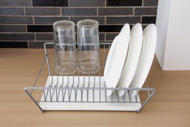 White dishes drying on metal dish rack
