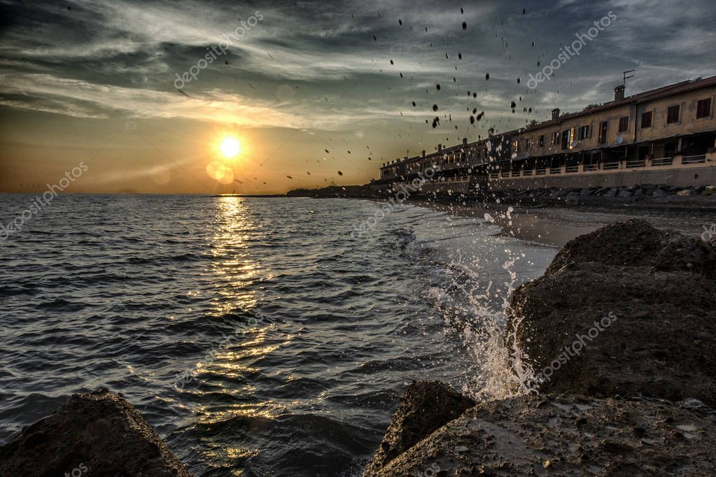 Sunset with a splash of water breaking on a rock in front of the Odescalchi Castle and a fisherman village, between the seaside resorts Ladispoli and Marina di San Nicola, on the coast of Lazio to the north of Rome, Italy