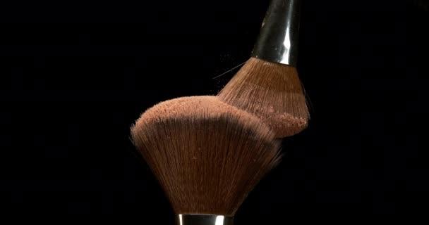 Make-up Brush spreading blush powder on black background, Slow motion 4K