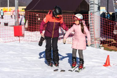 Sochi, Russia - January 7, 2018: Female ski instructor teaches skiing to small girl on snowy mountain slope in Gorky Gorod winter mountain ski resort.