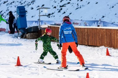 Sochi, Russia - January 7, 2018: Female ski instructor teaches skiing to little girl on snowy mountain slope in Gorky Gorod winter mountain ski resort.