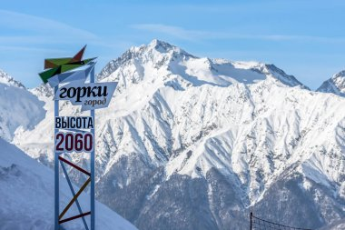Sochi, Russia - January 7, 2018: Big sign of Gorky Gorod mountain ski resort placed in Aibga cirque on 2060 m above s. l. on snowy winter Mount Chugush and blue sky background