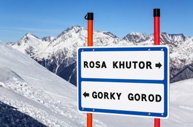 Sochi, Russia - January 20, 2013: Information navigation direction sign on metal plate bifurcating streams to Rosa Khutor and Gorky Gorod ski and snowboard resorts with mountain peak. United ski pass