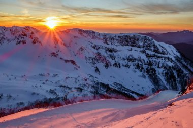 Beautiful scenic winter mountain sunset landscape of snowy Caucasus Mountains and ski slope of Gorki Gorod mountain ski resort in Sochi, Russia.