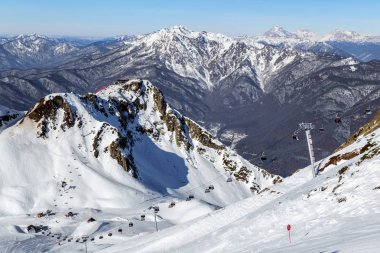Ski slopes and chair ski lifts in Gorky Gorod winter mountain ski resort on blue sky and snowy peaks scenic background. Beautiful winter landscape.