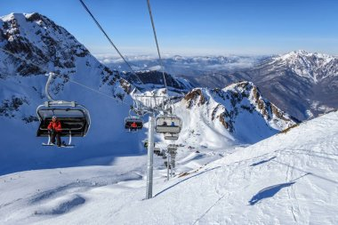 Sochi, Russia - January 20, 2013: Snowy Aibga mountain cirque ski slopes and chair ski lifts in Gorky Gorod winter ski mountain resort under blue sky on sunny day. Scenic Caucasus Mountains landscape.