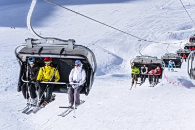 Sochi, Russia - January 20, 2013: Skiers and snowboarders ride on chair ski lift on sunny winter day on snowy ski slopes background
