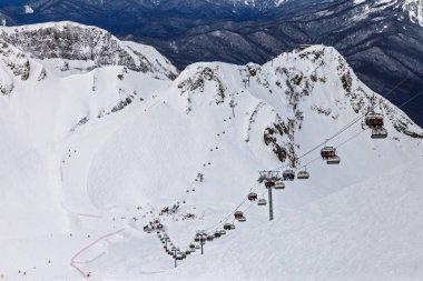 Skiers and snowboarders ride on ski lift on winter day. Ski slopes and tracks in Gorky Gorod mountain resort host ski and snowboard riders all winter long. Scenic landscape of snowy Caucasus Mountains