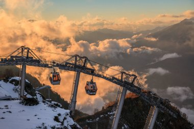 Cable car ski lifts in Gorky Gorod mountain ski resort can. Beautiful scenic sunset landscape. Sochi, Russia, Caucasus