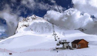 Snowy Aibga mountain peak, ski slopes and chair ski lift in Sochi, Russia. Winter Caucasus mountain wide blue sky panorama landscape