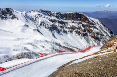 Ski track in Gorky Gorod winter mountain ski resort on blue sky and snowy rocks scenic background. Sochi, Russia, Caucasus Mountains