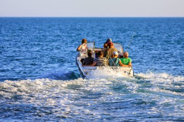 Anapa, Russia - June 11, 2012: People sail away on motor boat into open sea on sunny summer day. Tourist transportation service on Black Sea by Utrish village.