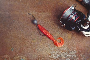 spinning fishing rods, fishing hooks, silicone baits on a wooden background with place for text, Photo for typography, poster, banner, postcard. Everything for fishing
