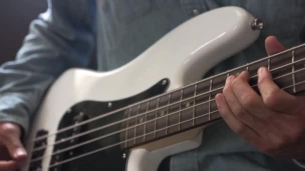 hudebník, který hraje na basu prstem ve studiu, zaostřená s selektivním zaměřením-hudební nástroje-koncepce hudební kompozice a tvořivost