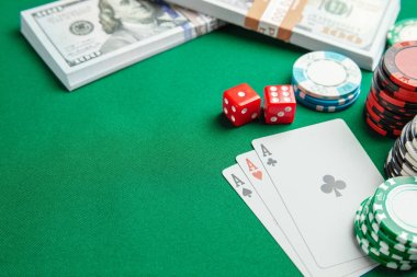 Concept of gambling in casino, sports poker. Playing cards with dice and colored chips with cash money dollars on green table