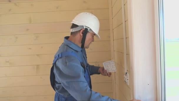 ingegnere elettrico professionista esegue linstallazione di prese elettriche e cablaggi in una nuova casa in legno