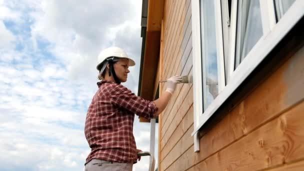 mladá žena maluje vnější stěnu nového dřevěného domu. proces Malování venkovského domu