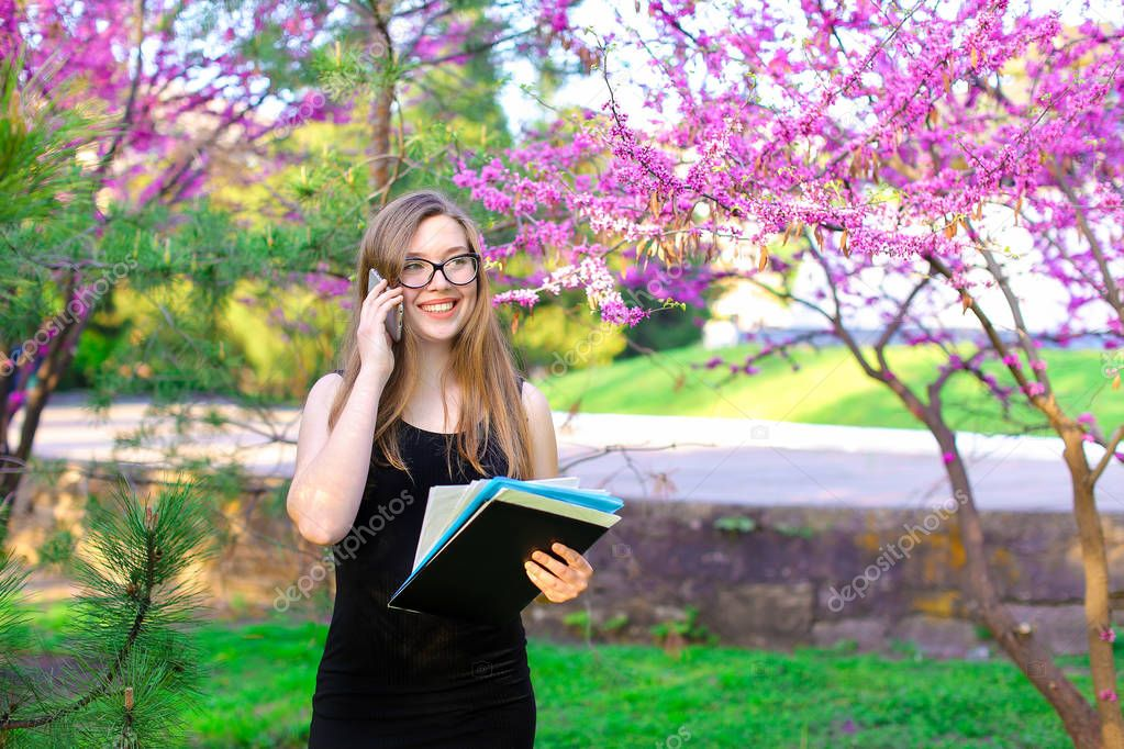 Pretty businesswoman talking with partner by smartphone near blooming trees.