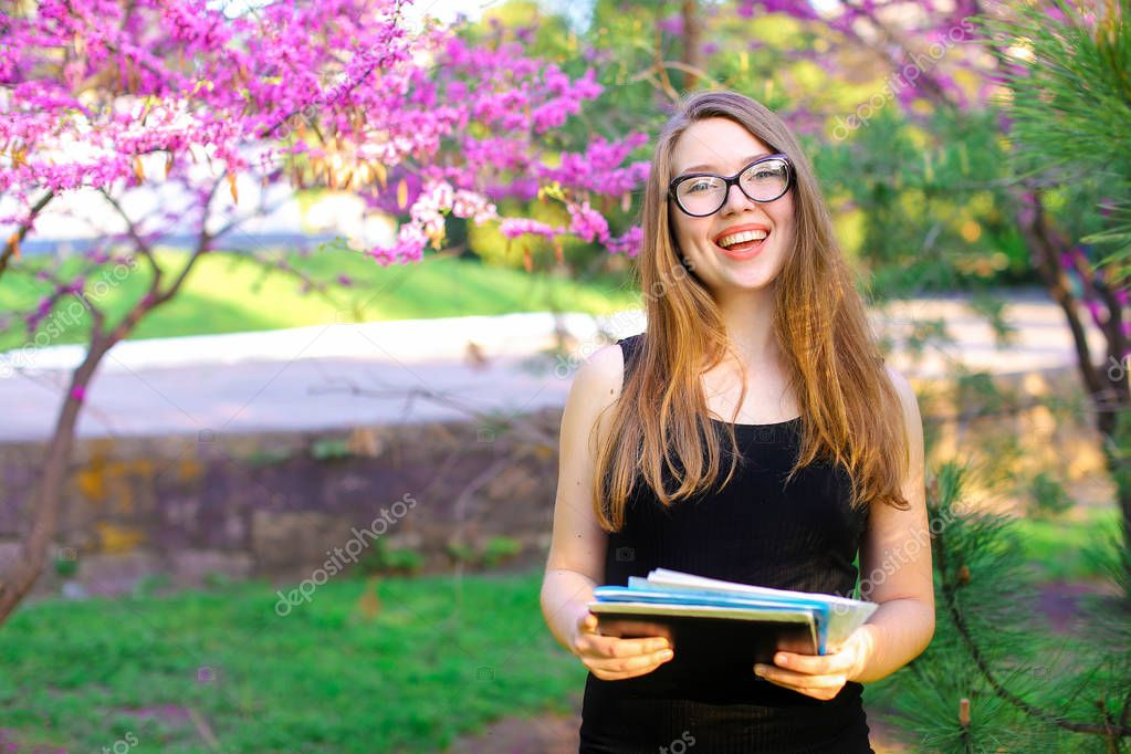 Female manager in glasses keeping documents near blooming trees in garden.