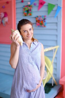 Young nice pregnant woman holding seashell to ear and standing near children house.