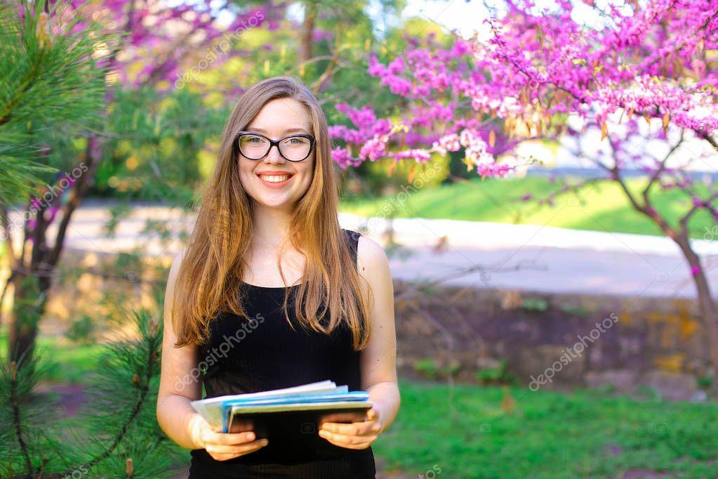 Female secretary in glasses keeping documents near blooming trees in garden.