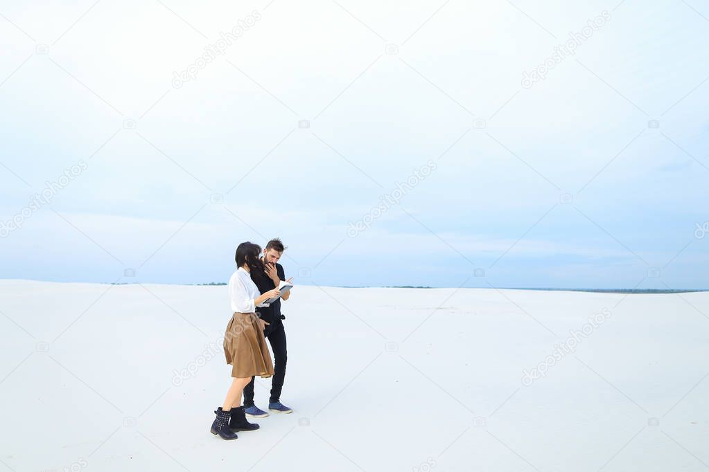Businessman walking with female secretary on snow with tablet and papers.