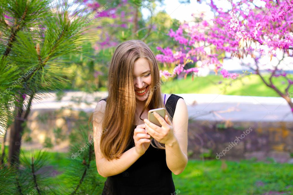 Cheerful woman using new smartphone in park with blooming trees background.
