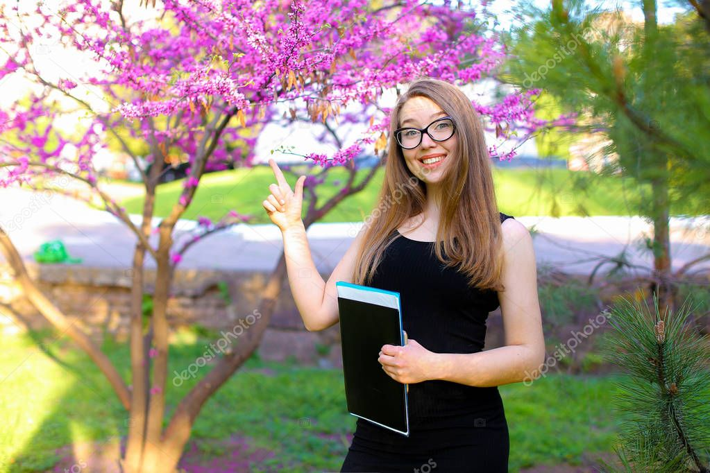 Pretty female secretary in glasses standing in blooming park and keeping with documents in black folder.