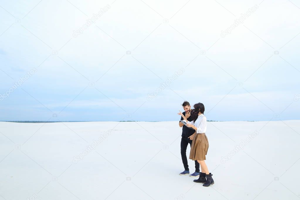 Young businessman walking with female secretary on snow with tablet and papers.