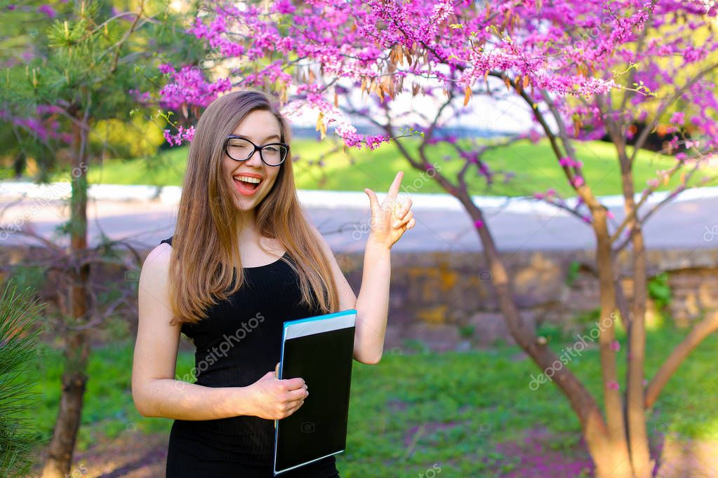 Cheerful female secretary in glasses standing in blooming park with documents in folder.
