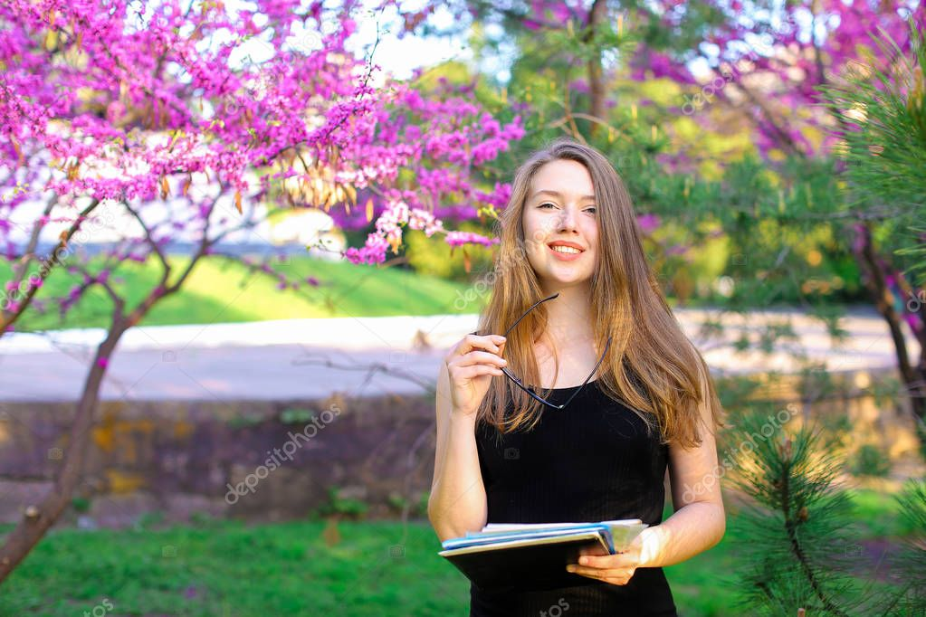 Businesslady standing near trees in blossom with documents and glasses.