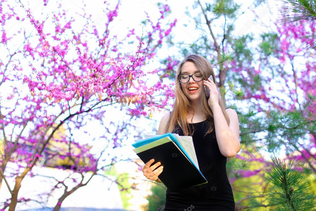 Young businesswoman in glasses talking by smartphone in blooming park with documents.