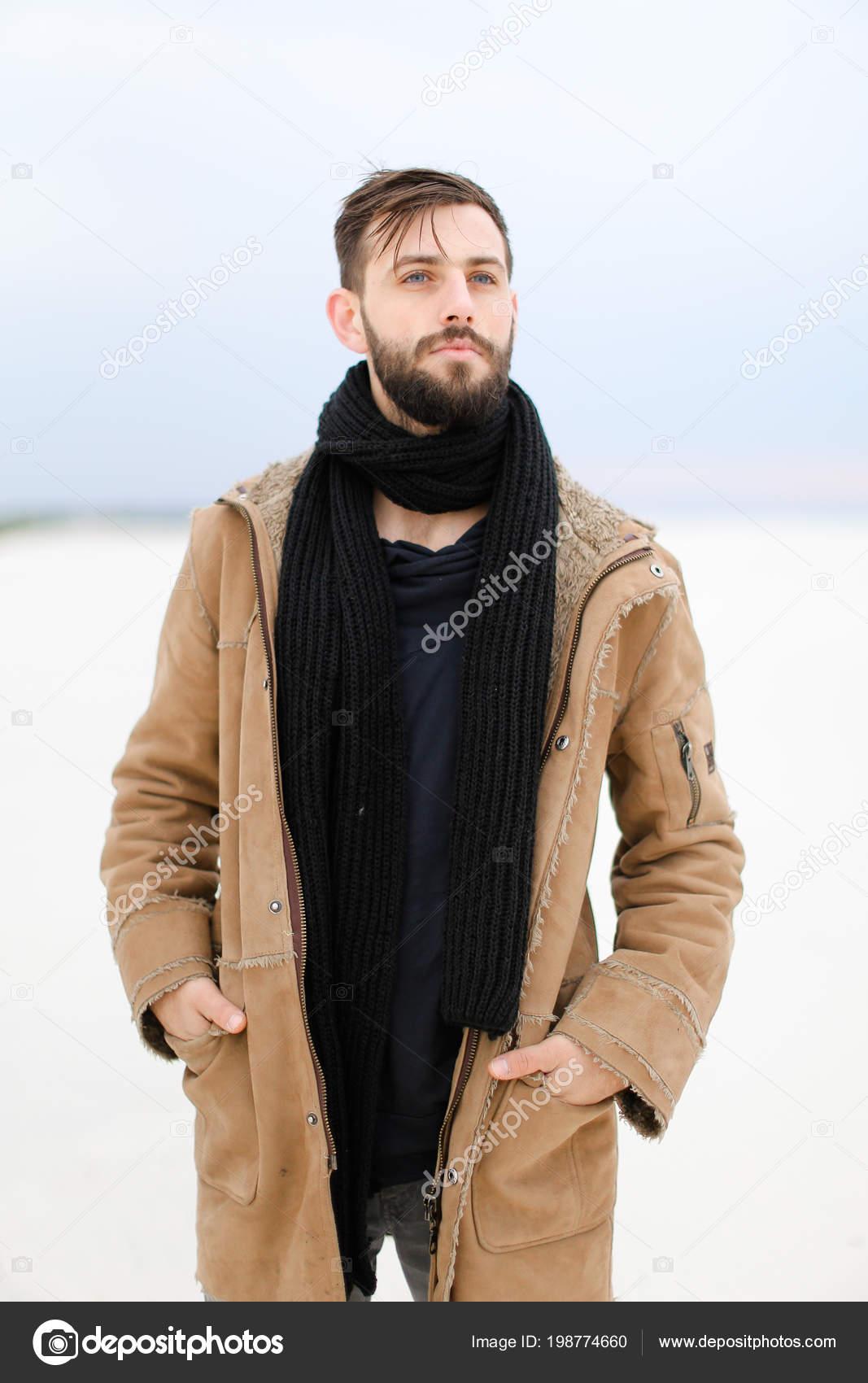 a543e32219f9 Personne de sexe masculin jeune européen avec barbe porte manteau et écharpe  debout dans le fond de blanc neige– images de stock libres de droits