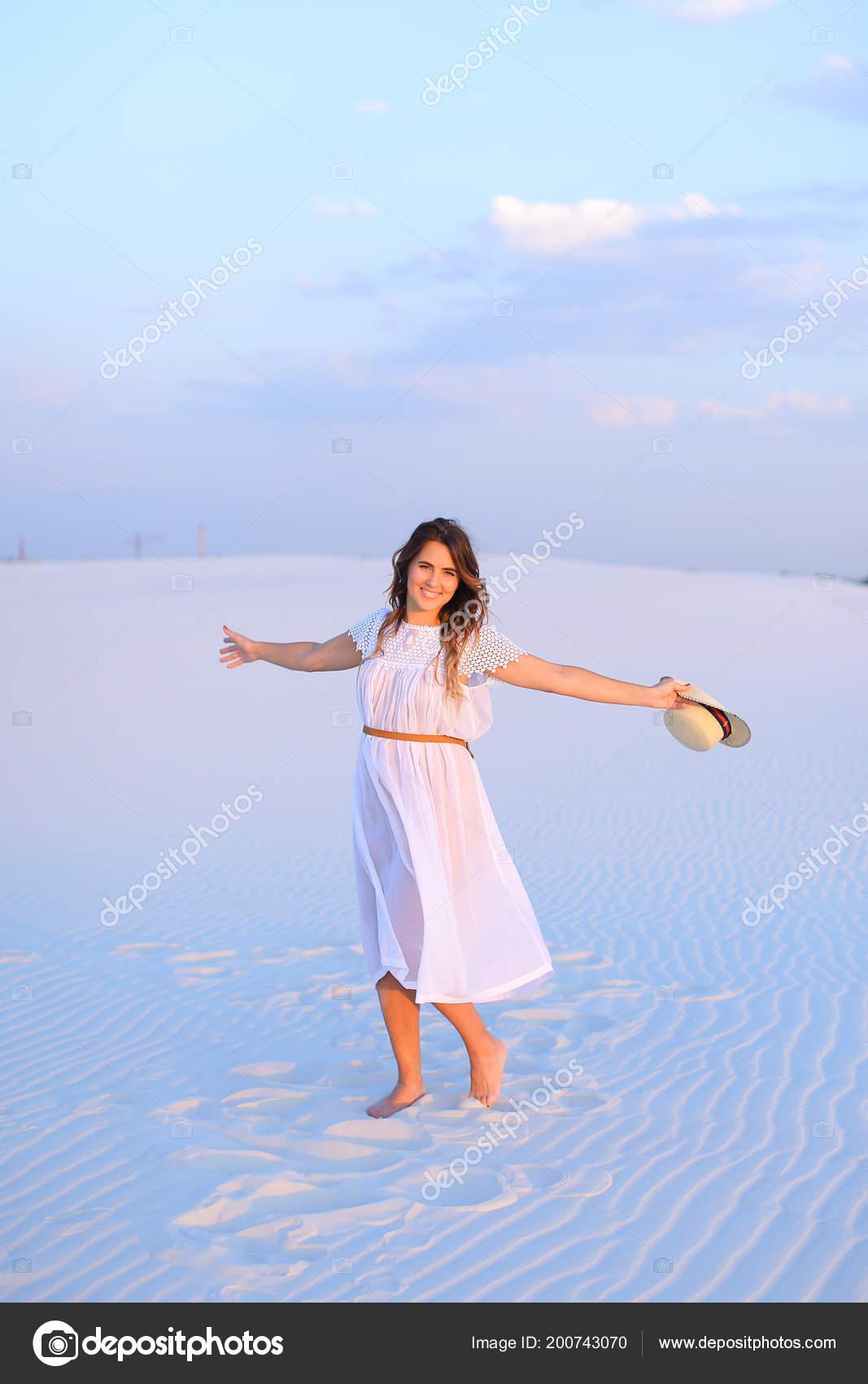 c5f3730fab17 Feliz mujer con vestido y sombrero de pie sobre la arena blanca en ...